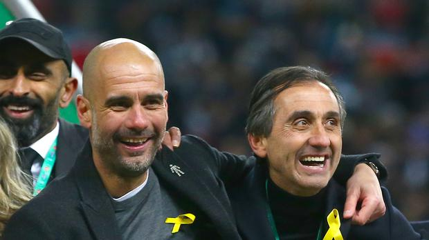 Pep Guardiola (left) has been fined for wearing a yellow ribbon on the touchline