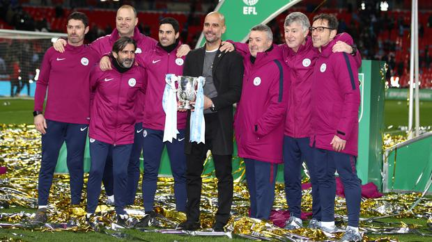 Pep Guardiola, centre, holds the Carabao Cup