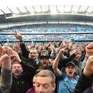 Fans invade the pitch after Manchester City's victory over Swansea