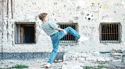 A boy playing with a football in front of a blood-soaked wall in Zadar during the Croatian War of Independence, November 1994 Colin Davey/Getty Images (Photo by Colin Davey/Getty Images)