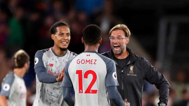 Liverpool manager Jurgen Klopp celebrates with Joe Gomez and Virgil van Dijk after the Premier League match at Selhurst Park, London.