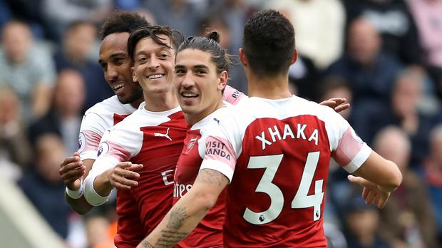 Mesut Ozil, second left, celebrates scoring Arsenal's second goal at Newcastle (Owen Humphreys/PA)