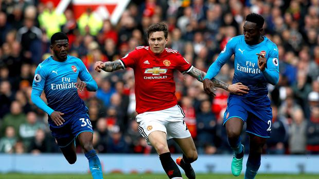 Manchester United's Victor Lindelof (centre) battle for the ball with Arsenal's Danny Welbeck (right) and Arsenal's Ainsley Maitland-Niles (left) during the Premier League match at Old Trafford, Manchester.