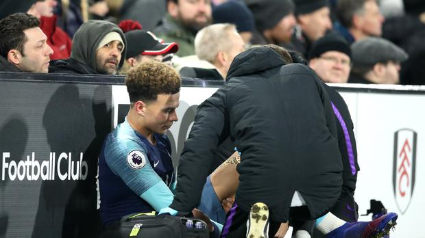 Tottenham Hotspur's Dele Alli receives medical treatment during the Premier League match at Craven Cottage, London.