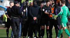 Mauricio Pochettino (centre) speaks to referee Mike Dean at the end of the match at Turf Moor (Martin Rickett/PA)