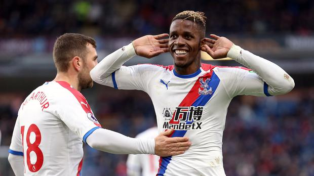 Crystal Palace's Wilfried Zaha, right, celebrates scoring his side's third goal of the game (Nigel French/PA)