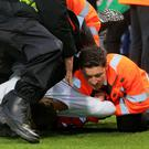 A fan is removed from the pitch by stewards and police during the match with Bournemouth (Mark Kerton/PA)