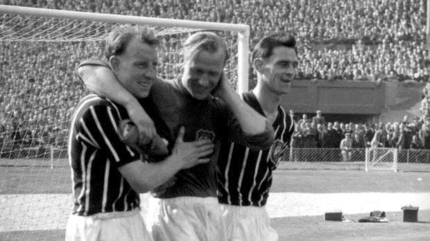 Former Manchester City goalkeeper Bert Trautmann, centre, is helped from the field in 1956 when he broke his neck (PA)