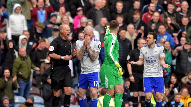 Aron Gunnarsson, second left, and Harry Arter, right, react after referee Mike Dean changes his mind about awarding Cardiff a penalty (Anthony Devlin/PA)