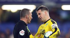 Burnley goalkeeper Tom Heaton speaks to referee Kevin Friend after being booked at Stamford Bridge (Adam Davy/PA)