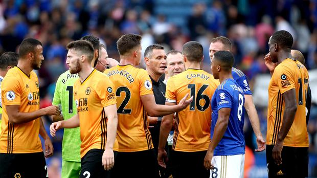Referee Andre Marriner speaks to Wolves players including Conor Coady, centre right, and Leander Dendoncker, centre left, after the game (Tim Goode/PA)