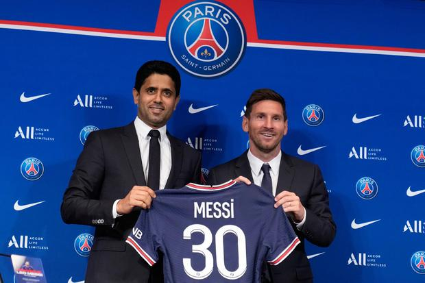 Lionel Messi, right, poses with his jersey with PSG president Nasser Al-Al-Khelaifi during a press conference today at the Parc des Princes stadium in Paris.