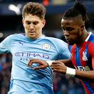 John Stones, left, battles with Crystal Palace forward Wilfried Zaha (Martin Rickett/PA)