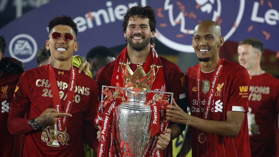 Fabinho, right, celebrates Liverpool's Premier League title success with Roberto Firmino, left, and Alisson Becker (Phil Noble/PA)