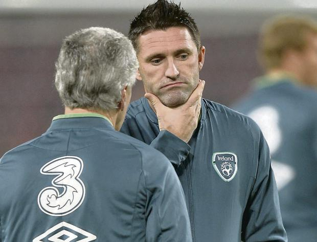 Ireland captain Robbie Keane in pensive mood alongside equipment officer Mick Lawlor after missing training last night