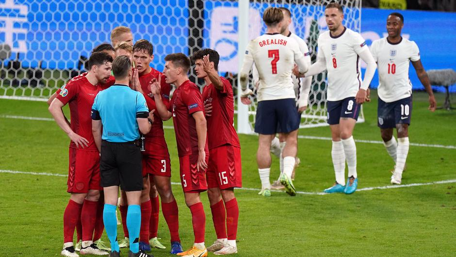 Denmark players surround referee Danny Makkelie after he awarded a penalty. (Mike Egerton/PA)