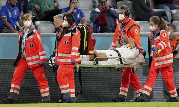 Italy's Leonardo Spinazzola is carried off on a stretcher (Matthias Schrader/AP)