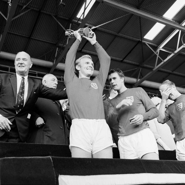 Bobby Moore lifts the Jules Rimet trophy at Wembley in 1966 (PA)