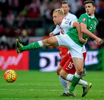 Ireland's Shane Long battles it out with Poland's Kamil Glik SPORTSFILE