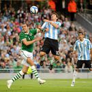 John O'Shea and Lionel Messi challenge for the ball during the Ireland vs Argentina match