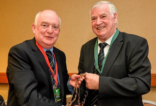 Outgoing FAI President Paddy McCaul, left, hands over the Presidential chain to newly elected FAI President Tony Fitzgerald at the association's AGM