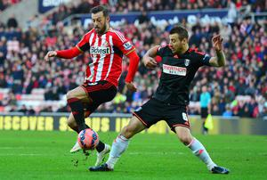 Steven Fletcher of Sunderland is tackled by Nikolay Bodurov of Fulham during the FA Cup Fourth Round match at Stadium of Light