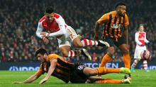 Alexis Sanchez of Arsenal is upended by Harry Maguire of Hull City