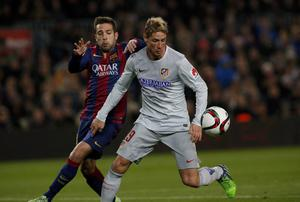 Atletico's Fernando Torres, right, fights for the ball against Barcelona's Jordi Alba during a Copa del Rey Quarterfinal match between FC Barcelona and Atletico Madrid