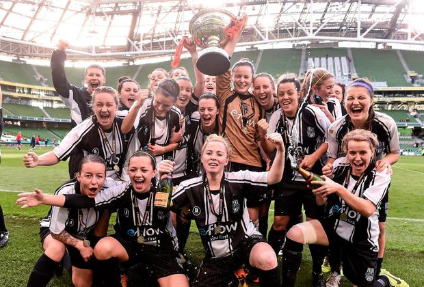 Raheny United players celebrate with the cup at the end of the game