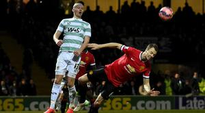 Kieffer Moore (L) of Yeovil and Jonny Evans of Manchester United fight for the ball during their FA Cup third round soccer match at Huish Park, Yeovil