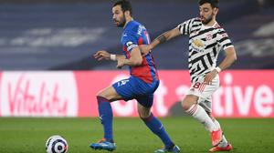 Bruno Fernandes gives chase to Luka Milivojevic in the goalless draw at Selhurst Park last night, a result which effectively rules Manchester United out of the Premier League title race. Photo: Reuters