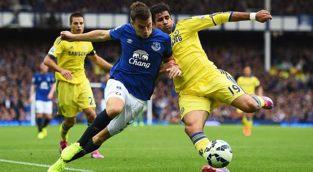 Diego Costa of Chelsea tackles Seamus Coleman of Everton