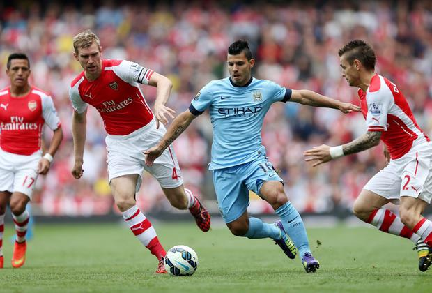Manchester City's Sergio Aguero (right) is challenged by Arsenal's Per Mertesacker and Mathieu Debuchy