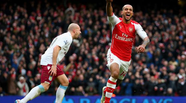Theo Walcott of Arsenal celebrates after scoring his team's third goal during the Barclays Premier League match between Arsenal and Aston Villa at the Emirates Stadium