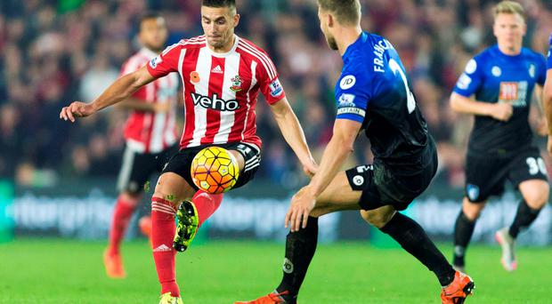 Southampton's Dusan Tadic (L) vies with Bournemouth's English defender Simon Francis during the match between Southampton and Bournemouth at St Mary's Stadium