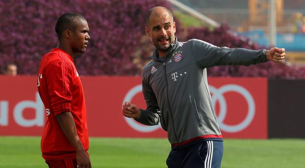 Pep Guardiola speaks with Douglas Costa during a Bayern Munich training camp in Doha