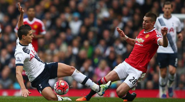 Spurs' Erik Lamela contests a ball with Manchester United's Morgan Schneiderlin