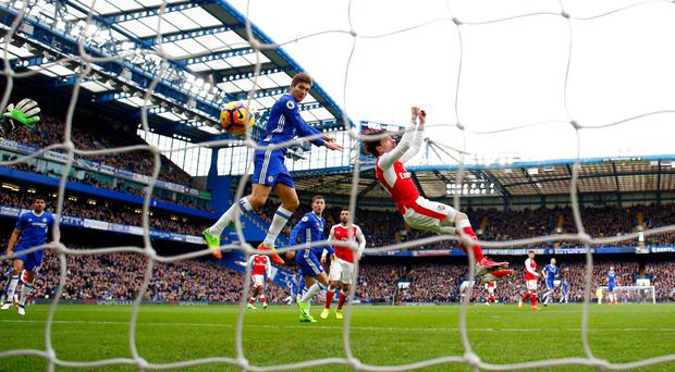 Marcos Alonso outjumps Hector Bellerin to head Chelsea into the lead against Arsenal in the Premier League leaders' 3-1 victory at Stamford Bridge yesterday. Photo: Getty Images