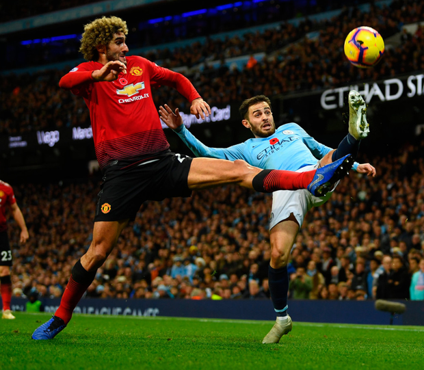 Blue is the colour: Bernardo Silva reaches the ball ahead of Marouane Fellaini. Photo: Getty