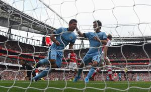 Sergio Aguero of Manchester City celebrates with team-mate David Silva after scoring the first goal during the Barclays Premier League match between Arsenal and Manchester City