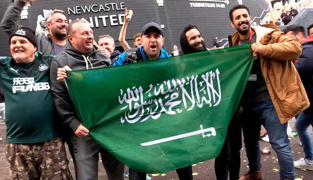 Jubilant Newcastle United fans hold a Saudi flag outside St James' Park whilst celebrating the club's Saudi takeover. Photo: PA Wire