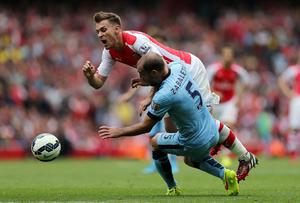 Arsenal's Aaron Ramsey (left) is tackled by Manchester City's Pablo Zabaleta during the Barclays Premier League match at the Emirates Stadium, London