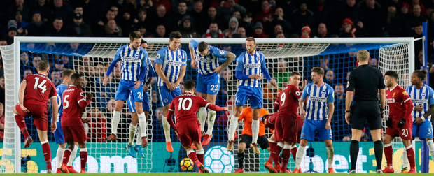 Philippe Coutinho deceives the Brighton wall with a low shot to scores his side's fourth goal