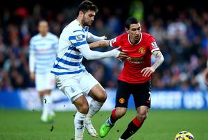 Angel di Maria of Manchester United battles for the ball wit Charlie Austin of QPR during the Barclays Premier League match between Queens Park Rangers and Manchester United