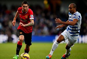Angel di Maria of Manchester United runs with the ball under pressure from Karl Henry of QPR during the Barclays Premier League match between Queens Park Rangers and Manchester United