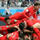Harry Kane, hidden, is mobbed by team-mates after his injury-time goal gave England victory against Tunisia (Owen Humphreys/PA)
