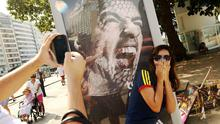 A woman takes a photo next to an advertisement featuring Uruguay's Luis Suarez baring his teeth on Copacabana Beach in Rio de Janeiro, Brazil. Photo credit: Mario Tama/Getty Images