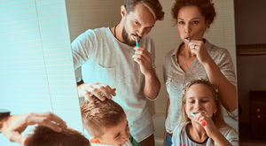 mother and father brushing teeth with their children
