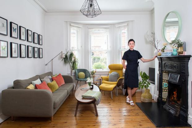 Wedding planner Kate O'Dowd in her living room. The red-brick house dates from 1870 and has lovely Victorian features, such as the high ceilings and mantlepiece. These work well with her funishings, many of which are mid-century modern. Photo: Tony Gavin