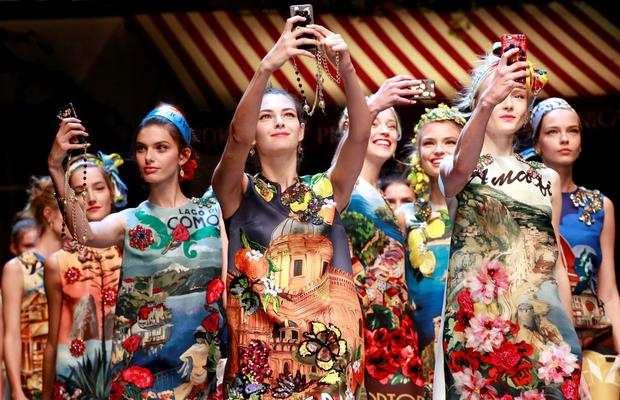 Models take selfie with mobile phones during the parade at the end of the Dolce & Gabbana Spring/Summer 2016